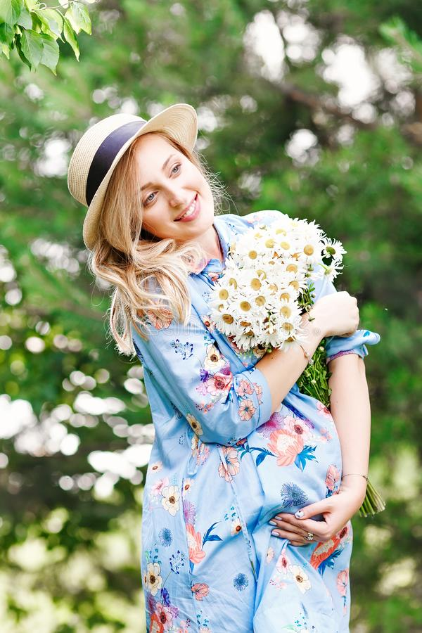 Close up view of beautiful pregnant woman in field holding bouquet and smile. Relax in nature royalty free stock photos