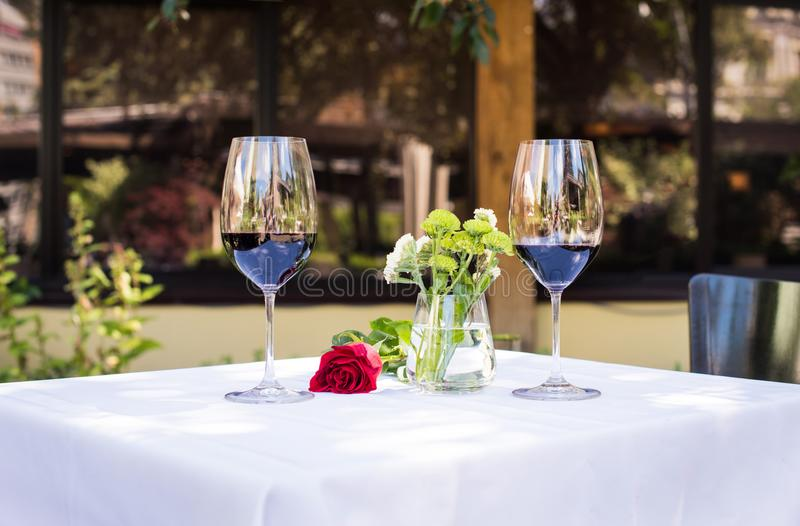 Close-up view of beautiful red rose flower with wine at table stock image