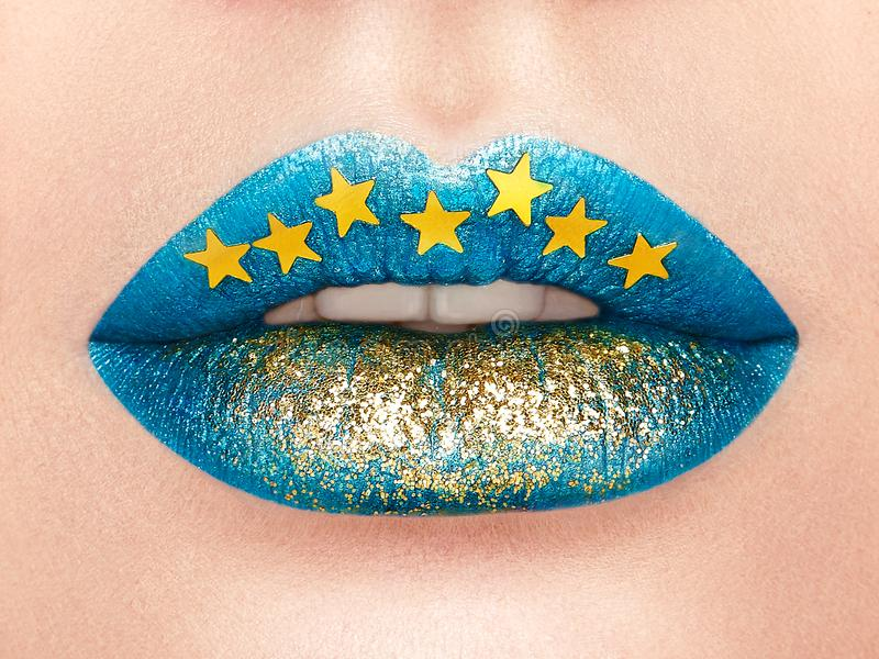 Close up view of beautiful woman lips with blue lipstick. Open Mouth with white Teeth. Cosmetology, drugstore or Fashion Makeup Concept Gold stars. Beauty stock image