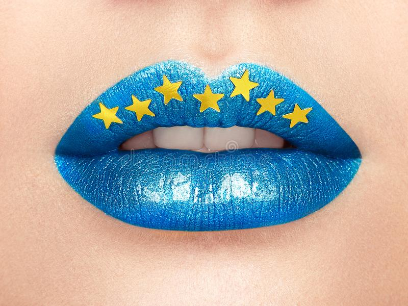 Close up view of beautiful woman lips with blue lipstick. Open Mouth with white Teeth. Cosmetology, drugstore or Fashion Makeup Concept Gold stars. Beauty stock photo