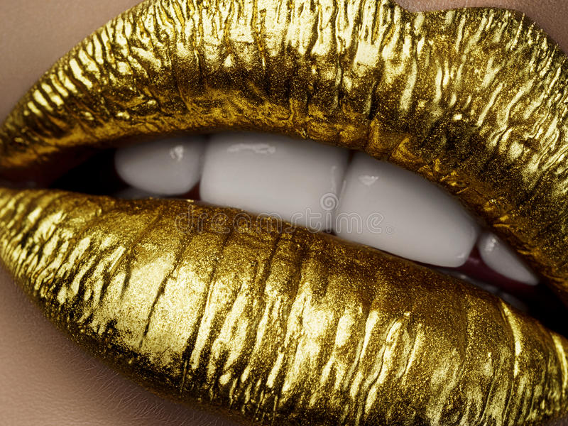 Close up view of beautiful woman lips with golden metallic lipstick. Open mouth with white teeth. Cosmetology, drugstore or fashion makeup concept. Beauty stock photo