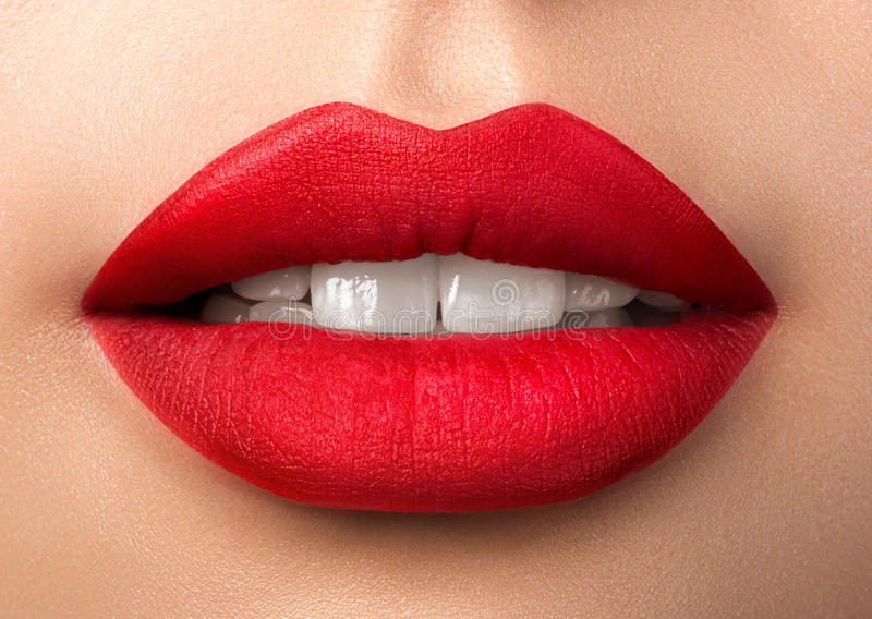 Close up view of beautiful woman lips with red matt lipstick. Close up view of beautiful woman lips with purple matt lipstick. Open mouth with white teeth royalty free stock image