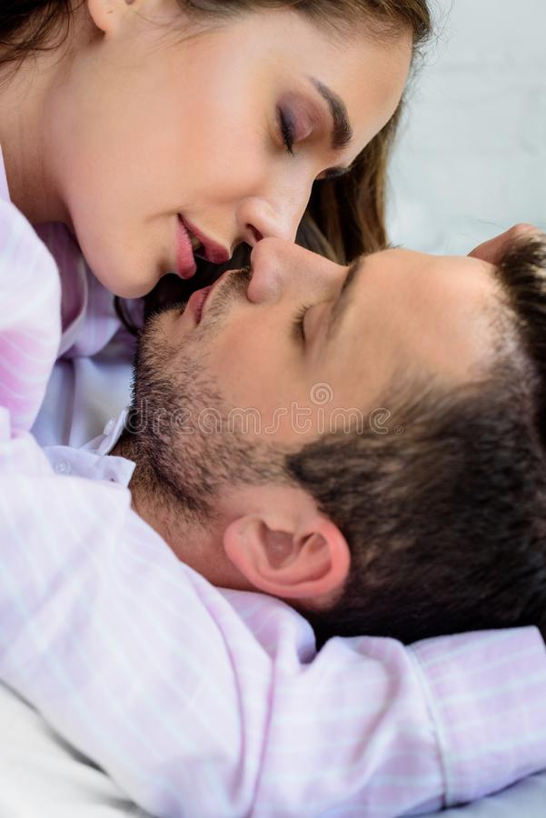 Close-up view of beautiful young couple in love kissing. At home stock photography