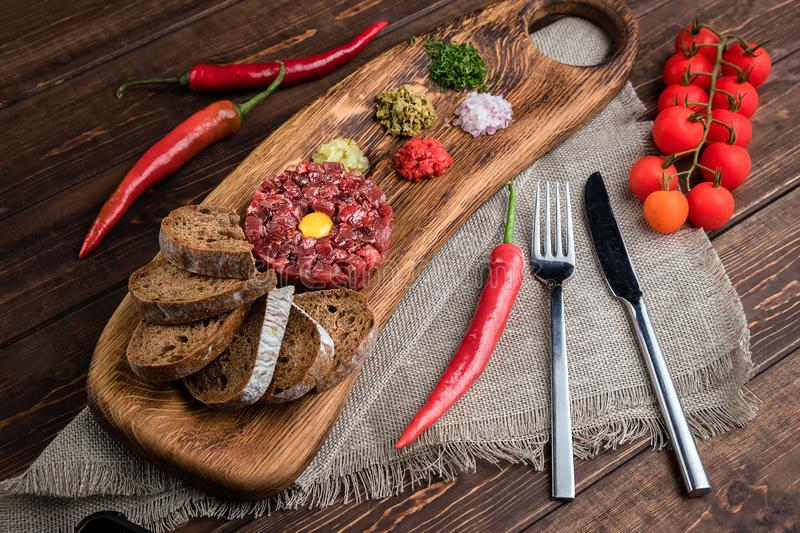 Close-up view on Beef Tartar with a raw egg yolk, rye bread and chilis on a wooden board and rough cloth with spoon and fork. Shot stock photography