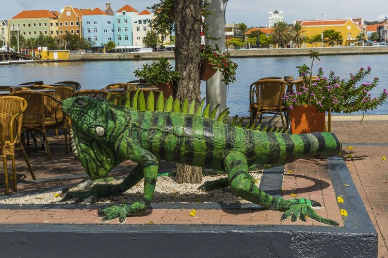 Close up view of big green iguana figure as decoration of outdoor restaurant. Saint Anna Bay and colorful buildings on background. Willemstad. Curacao royalty free stock photo