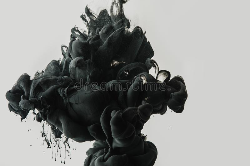 close up view of black paint splash in water isolated on gray stock photos