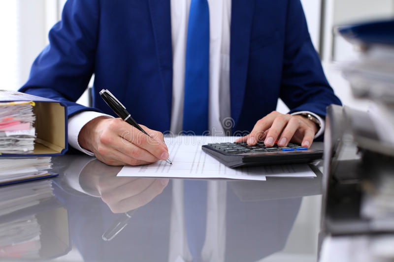 Close up view of bookkeeper or financial inspector hands making report, calculating or checking balance stock image