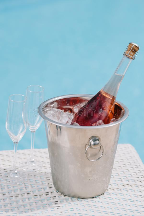 close-up view of bottle of champagne in bucket with ice and two empty glasses royalty free stock photo