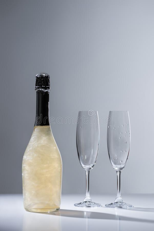 close up view of bottle of champagne and empty glasses stock photos