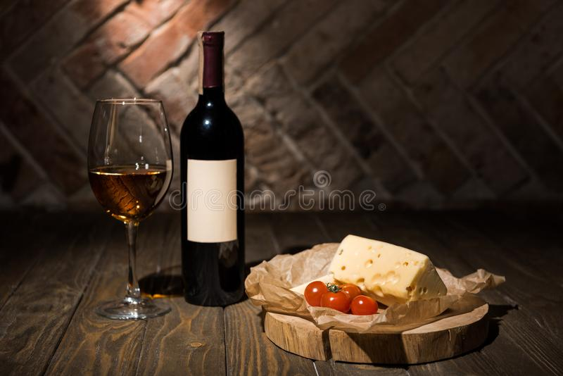 Close up view of bottle and glass of wine with cheese and cherry tomatoes on baking paper on wooden. Decorative stump stock photos