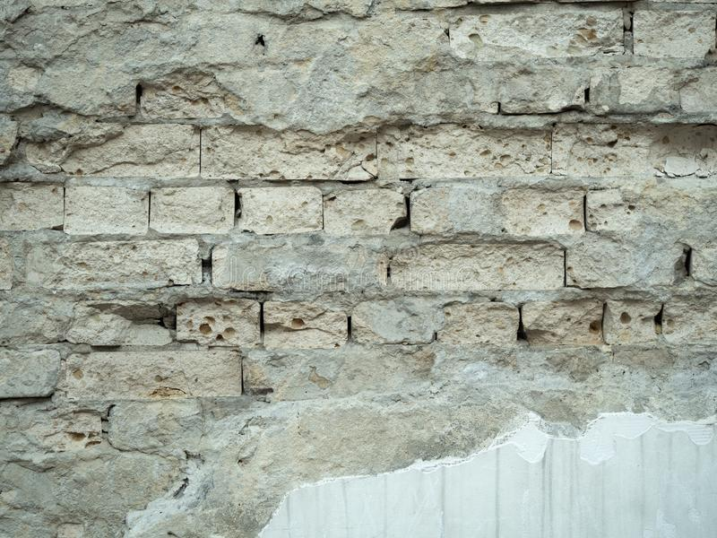 Close up view on brickwall with peeled off white plaster. Ancient brickwall background. An old ruined wall texture. Grey stock photography