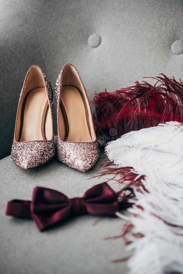 close up view of bridal shoes, grooms bow tie and feathers for rustic wedding royalty free stock image