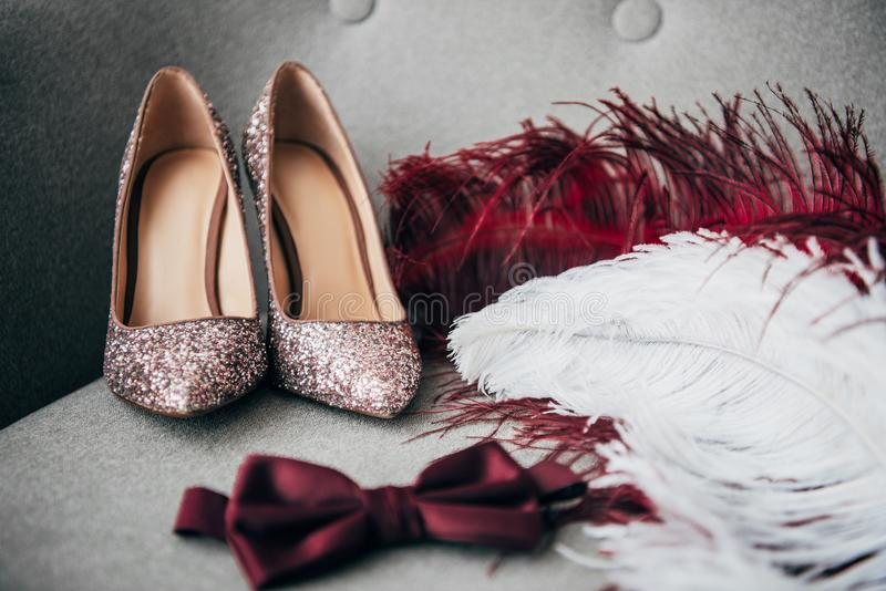 close up view of bridal shoes, grooms bow tie and feathers for rustic wedding stock images