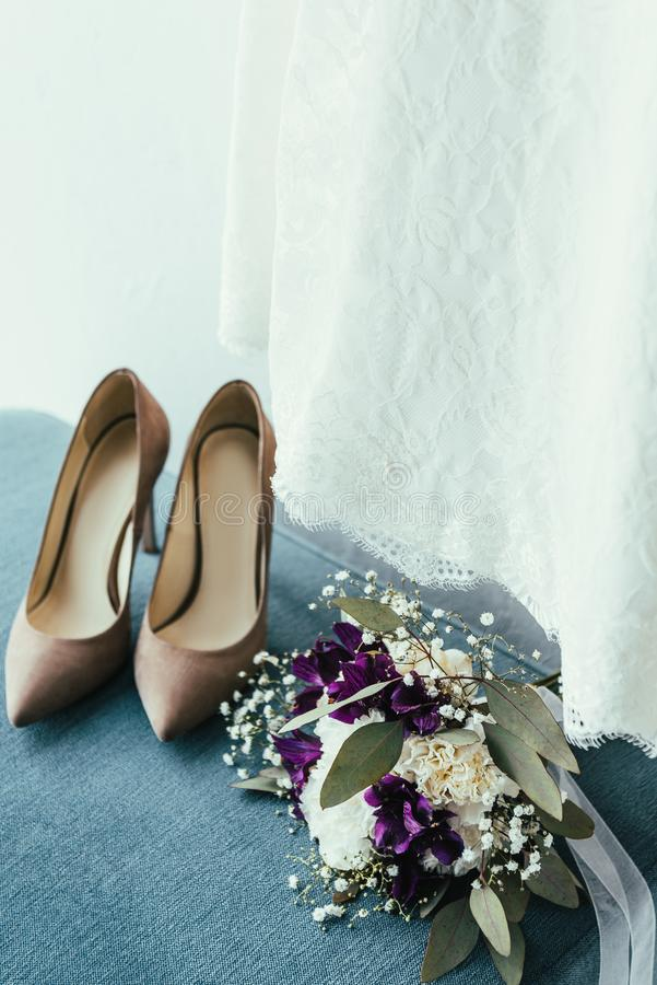 close up view of bridal shoes, wedding bouquet and dress royalty free stock image