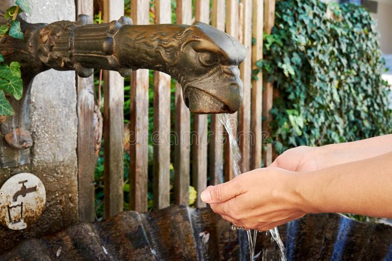 A close-up view of a bronze fountain with running water in Salzburg and a drinking woman washing her hands - Austria. In Europe royalty free stock images