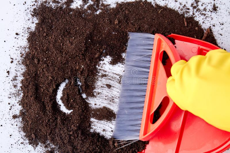 Close up view of broom sweeping floor with soil. stock images