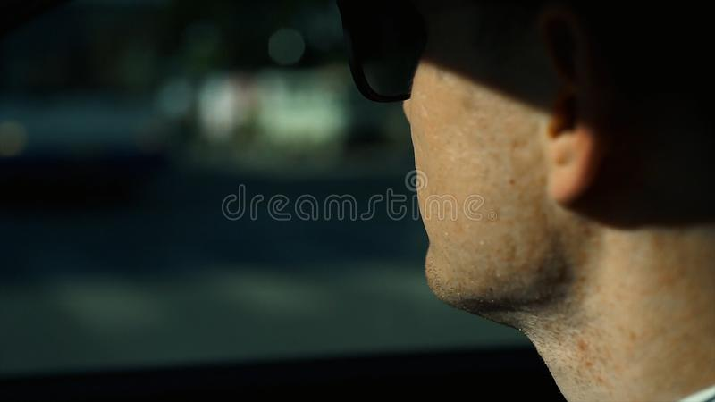 Close up view of businessman looking away while sitting on the back seat of a car. Stock. Business trip and people royalty free stock images