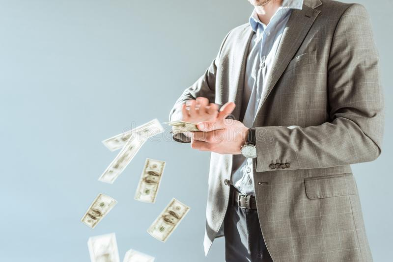 Close-up view businessman throwing money. On grey royalty free stock photo