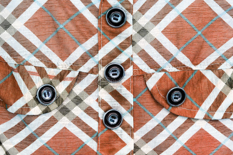 Close up view of a button over checked shirt. For background stock images