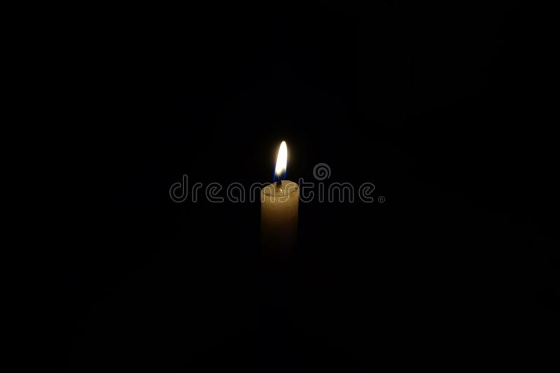 Close up view of a candle light blaming and glowing brightly in the dark night is a source of light. Close view candle light blaming glowing brightly dark night royalty free stock photo
