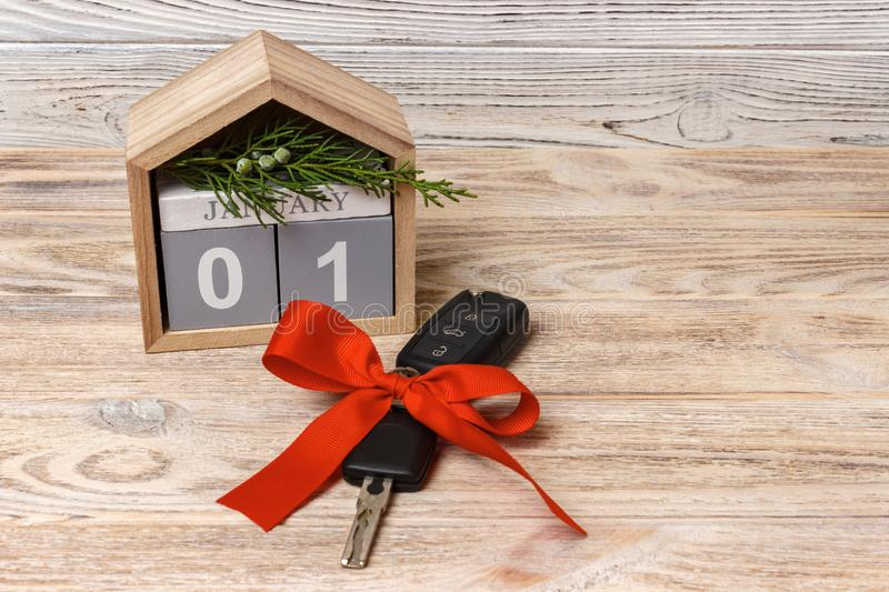 Close-up view of car keys with red bow as present and calendar on wooden background on wooden background royalty free stock photo