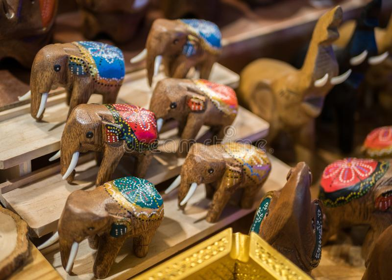 Carved wooden elephants selling in the souvenirs stall at Ratchada Rot Fai Train Night Market Bangkok royalty free stock photo