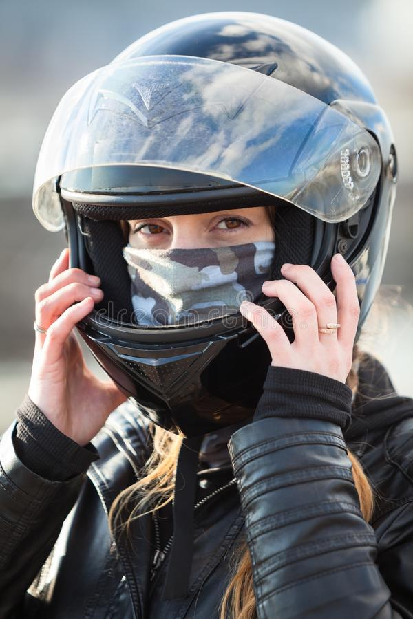 Close up view at Caucasian woman motorcyclist wearing crash black helmet on head stock image
