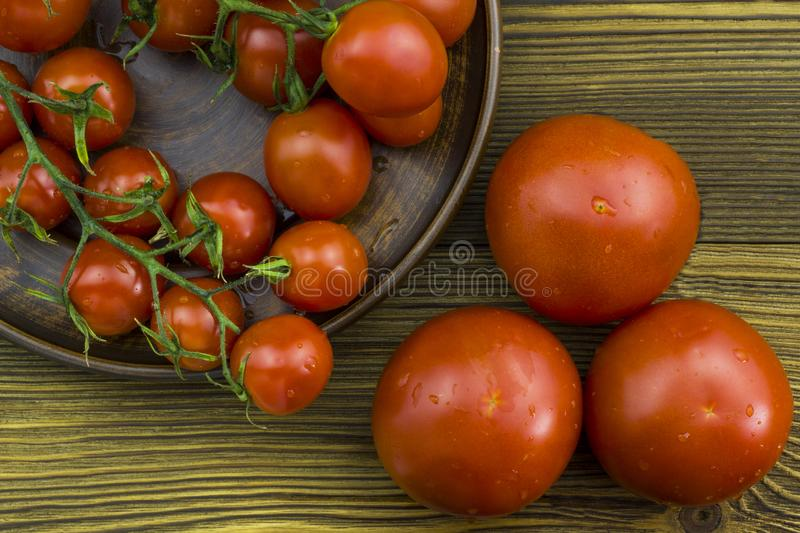 Close up view of cherry tomatoes bunch with water drops in a plate on a wooden background. Healthy food concept stock photo