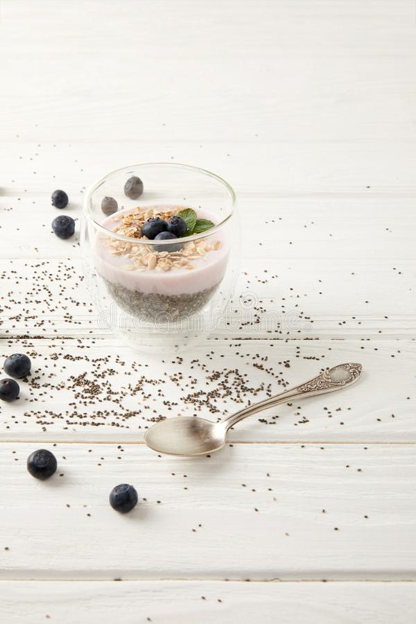 close up view of chia pudding dessert with blueberries and oatmeal on white wooden surface royalty free stock image