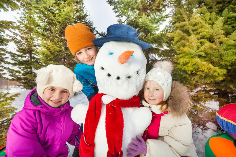 Close-up view of children sitting close to snowman stock image