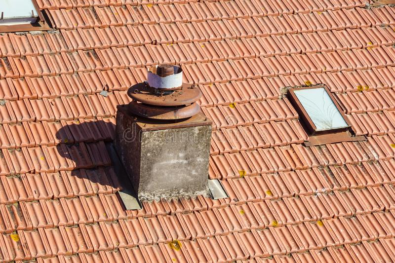 A close up view of a chimney on top of red roof tiles stock photos