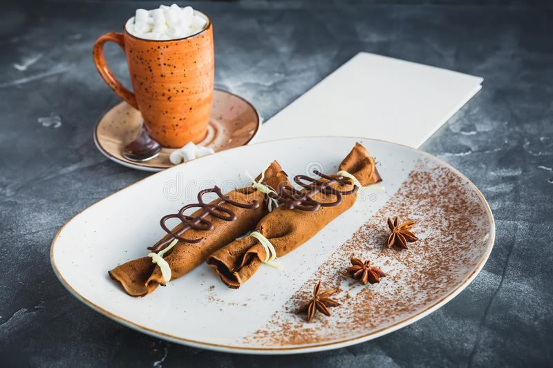 Close up view of chocolate pancakes with cinnamon, anise and cup of coffee with marshmallow. Paper menu with copy space royalty free stock photography