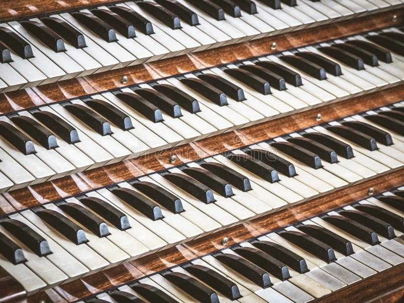 Close up view of a church pipe organ with four keyboards stock image