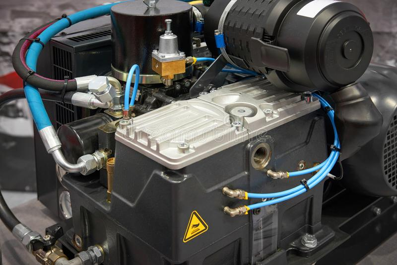 Close up view on clean new air compressor with electric motor, filter, rubber hoses, pneumatic and hydraulic components. Turbo com royalty free stock images