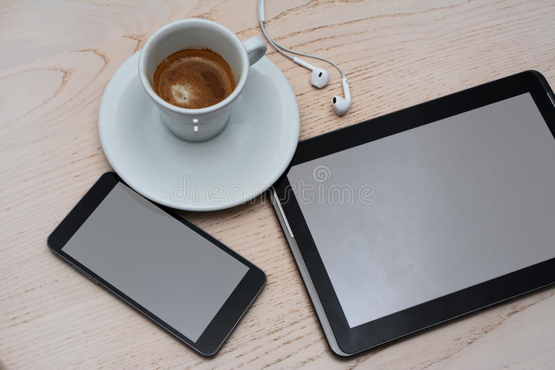 Close up view of coffee, earphones, tablet and cellphone on wooden background. royalty free stock photos