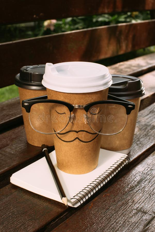 Close up view of coffee to go, eyeglasses and notebook. On wooden bench royalty free stock photos