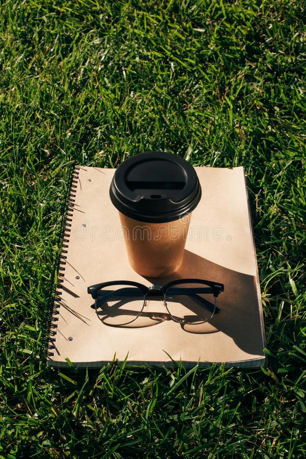 Close up view of coffee to go, notebook and eyeglasses. On green grass stock photography