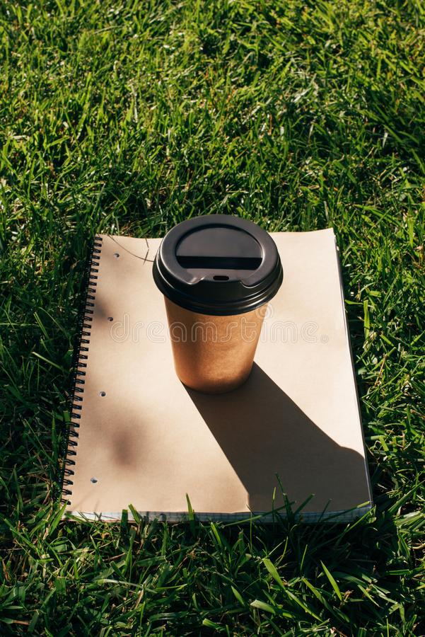 Close up view of coffee to go and notebook. On green grass royalty free stock photos