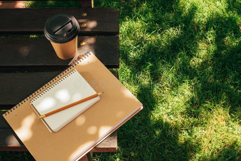 Close up view of coffee to go and notebooks with pencil. On wooden bench stock photography