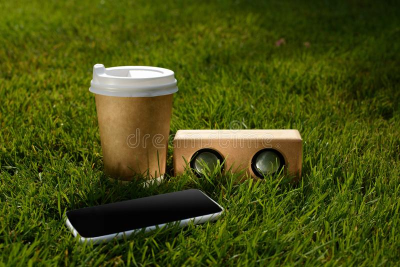 Close up view of coffee to go, smartphone and audio speaker. On green grass stock photo