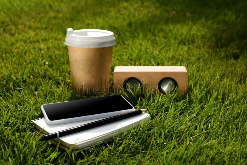 Close up view of coffee to go, smartphone, notebook and audio speaker. On green grass royalty free stock image