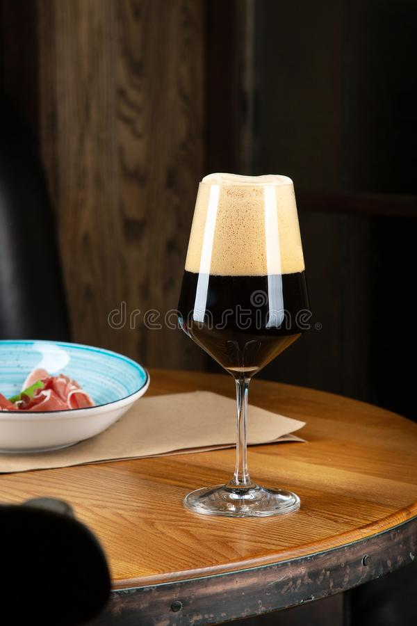 Close up view on cold dark craft beer in a glass with snack at bar on table. Bar image cocnept with copy space for logo or brand. royalty free stock images