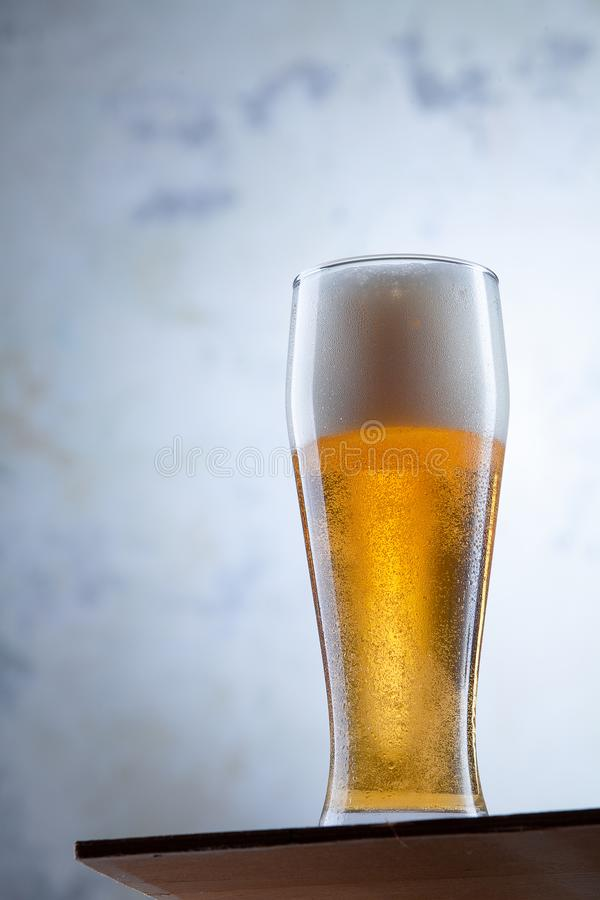 Close up view on cold glass of beer stands in front of a concrete wall. Alcohol cold drinks. Glass of light beer. Pub concept royalty free stock photo