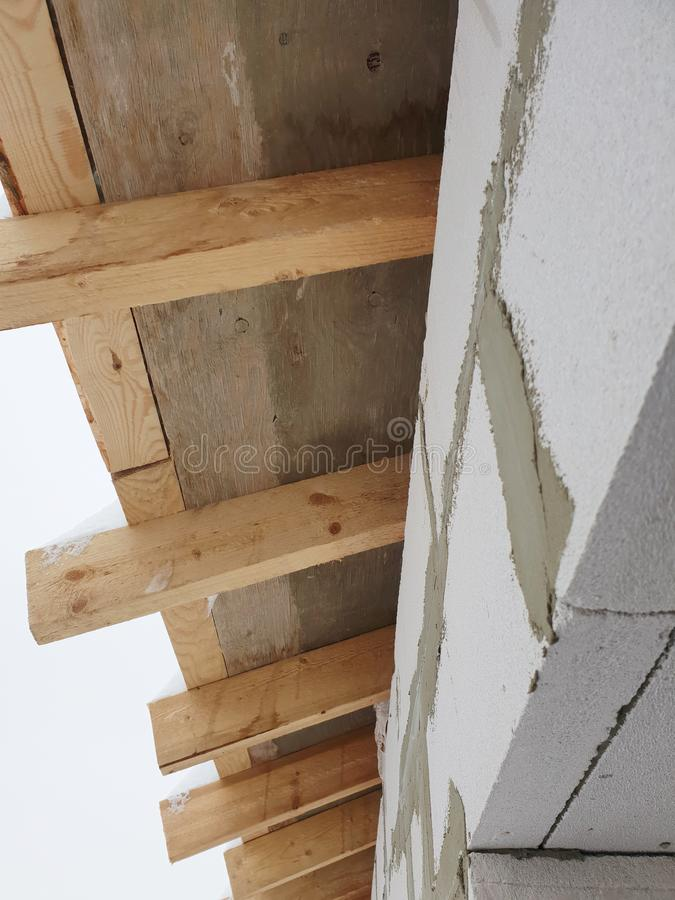 Close-up view of corner of house with scaffolding, where preparatory work is carried out before covering roof of final roof. Concrete, rafter, joist royalty free stock photo