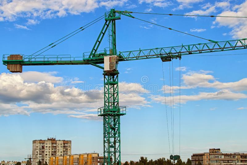 Close-up view of crane against blue sky with beautiful white clouds. Green tower crane building the new residential building. Construction site, Kyiv, Ukraine royalty free stock photography