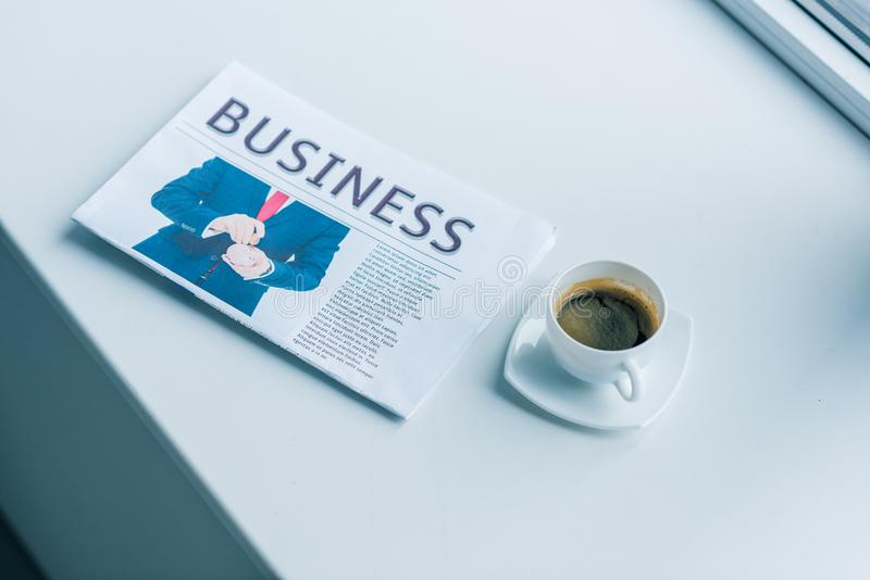 Close up view of cup of coffee and business newspaper. On white surface royalty free stock images