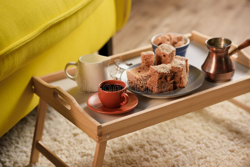 Close up view of cup of coffee, jag of cream, pieces of cake and brown sugar on wooden tray. In room royalty free stock images
