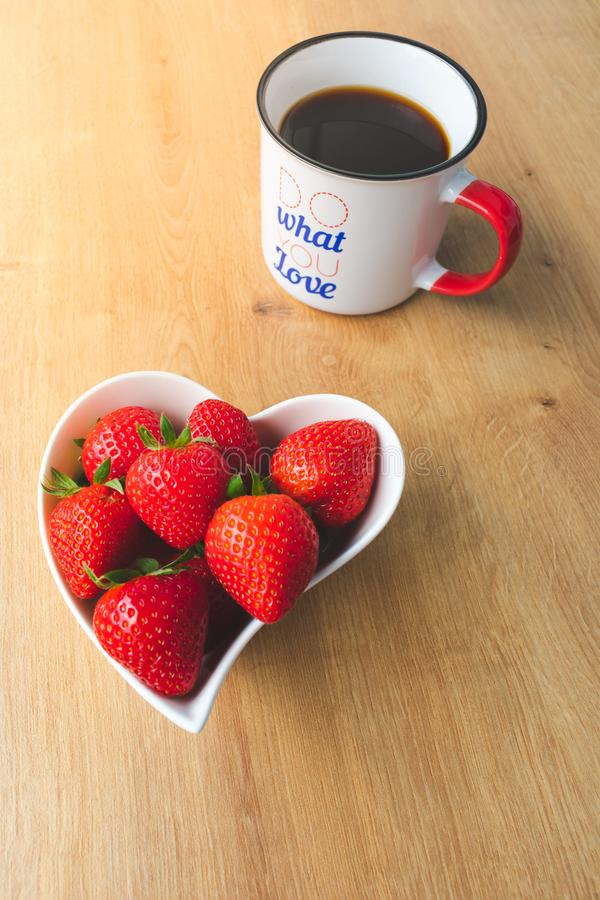 Cup of coffee and fresh strawberries on wooden table. Close up view of a cup of coffee with the phrase Do what you love and a heart shaped white bowl with fresh stock images