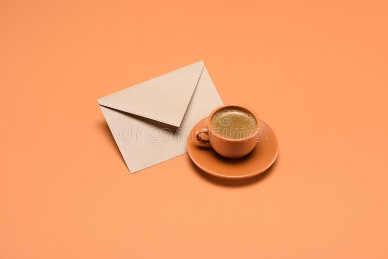 Close up view of cup of coffee on saucer and envelope. Isolated on peach royalty free stock images
