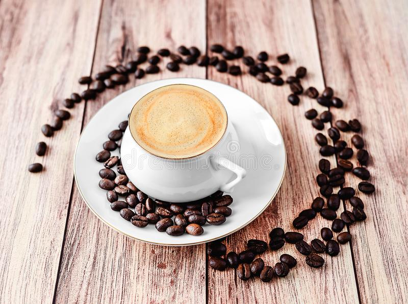 Close-up view of a cup of hot coffee on wooden rustic table with spilled coffee beans. Space for text, brazilian, grain, texture, arabic, aroma, aromatic royalty free stock photography